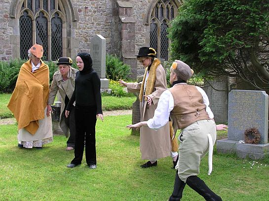 Actors in animal costume in a churchyard